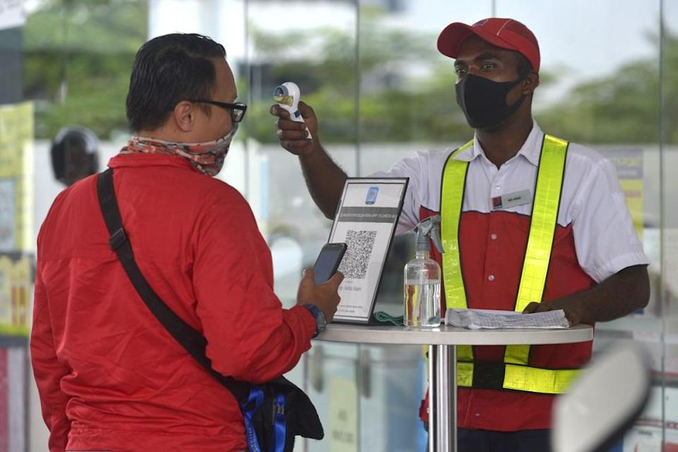 A customer gets his temperature checked before entering the premises of a petrol station in Setia Alam November 10, 2020. ― Picture by Miera Zulyana