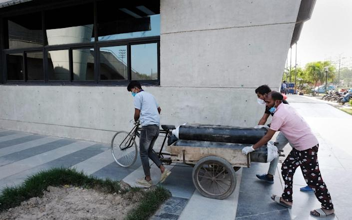 Health workers wheel a cart of oxygen tanks to a ward at the Covid-19 Care Center set up at the Commonwealth Games Village Sports Complex in New Delhi, India - T. Narayan/Bloomberg