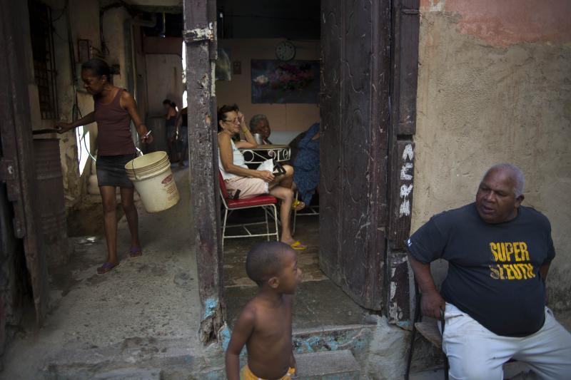 In this April 12, 2014 photo, people talk on the doorstep of their house in Havana, Cuba. Official government statistics show new construction has actually declined since Raul Castro assumed the presidency from his older brother Fidel in 2008. (AP Photo/Ramon Espinosa)