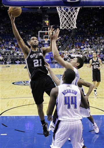 San Antonio Spurs' Tim Duncan (21) shoots over Orlando Magic's Nikola Vucevic, of Montenegro, and Andrew Nicholson (44) during the first half of an NBA basketball game, Wednesday, Nov. 28, 2012, in Orlando, Fla. (AP Photo/John Raoux)