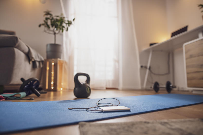 Power bank on yoga mat in living room with kettlebell and exercise equipment