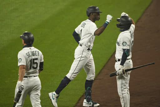 Seattle Mariners' Kyle Lewis, center, is greeted by Evan White, right, as Kyle Seager (15) looks on after Lewis hit a two-run home run against the Oakland Athletics during the fifth inning of the first baseball game of a doubleheader, Monday, Sept. 14, 2020, in Seattle. (AP Photo/Ted S. Warren)