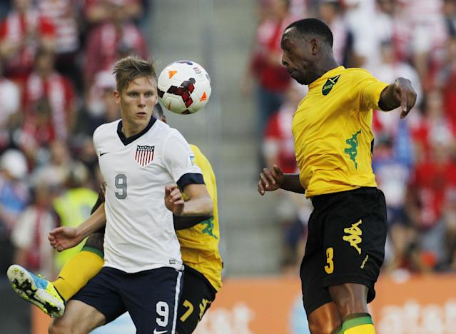 U.S. forward Aron Johannsson (9) and Jamaica defender Lloyd Doyley (3) attempt to control the ball in the first half of a World Cup qualifier soccer match at Sporting Park in Kansas City, Kan., Friday, Oct. 11, 2013. (AP Photo/Colin E. Braley)
