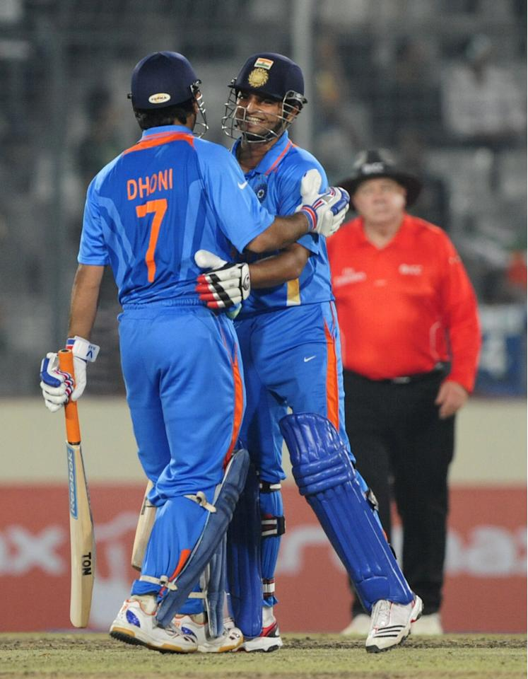 Indian batsman Suresh Raina (R) hugs his captain Mahendra Singh Dhoni (L) after India won the one day international (ODI) Asia Cup cricket match against Pakistan at The Sher-e-Bangla National Cricket Stadium in Dhaka on March 18, 2012. India defeated Pakistan by six wickets and Virat Kohli smashed a 148-ball 183 as India achieved the stiff 330-run target with 13 balls to spare in the day-night match, the first between the two teams since the World Cup semi-final at Mohali in March, 2011. AFP PHOTO/Munir uz ZAMAN (Photo credit should read MUNIR UZ ZAMAN/AFP/Getty Images)