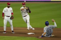 Cincinnati Reds second baseman Kyle Farmer (52) turns a double play during the seventh inning of a baseball game against the Kansas City Royals at Great American Ballpark in Cincinnati, Tuesday, Aug. 11, 2020. (AP Photo/Bryan Woolston)