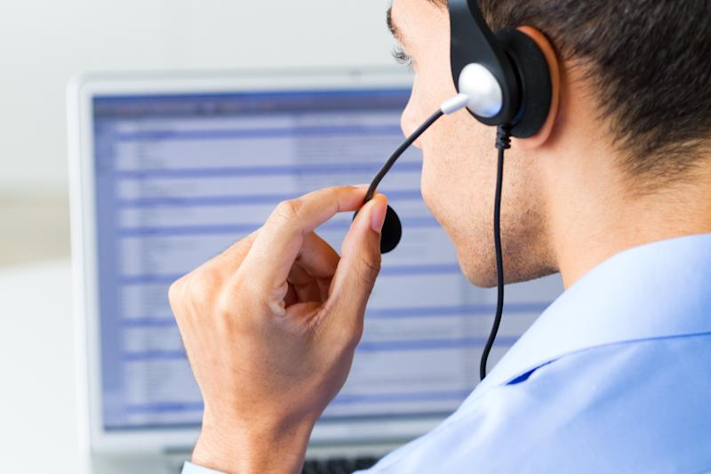 A customer service representative works in front of a screen.