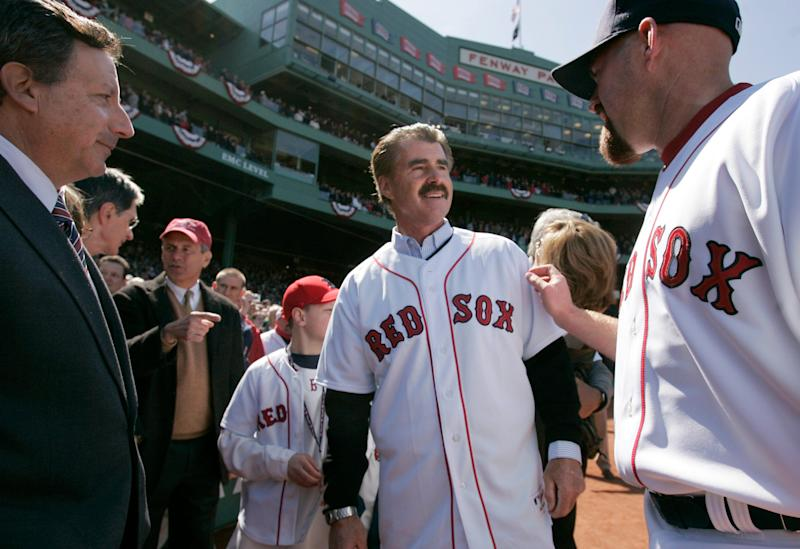 Bill Buckner, center, is greeted by Red Sox's Kevin Youkilis, right, and Red Sox Chairman and co-owner Tom Werner, left, at Fenway Park during the 2008 home-opener.