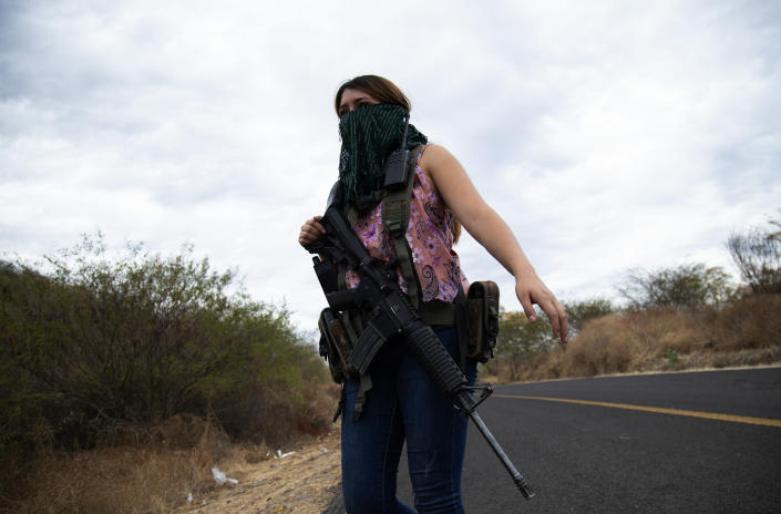 """An armed woman who goes by the nickname """"La Guera,"""" and who says she is a member of a female-led, self-defense group, patrols the edge of her town El Terrero, where it shares a border with the town of Aguililla, in Michoacan state, Mexico, Thursday, Jan. 14, 2021. In other towns nearby, residents have dug trenches across roadways leading into neighboring Jalisco state, to keep attackers out. (AP Photo/Armando Solis)"""