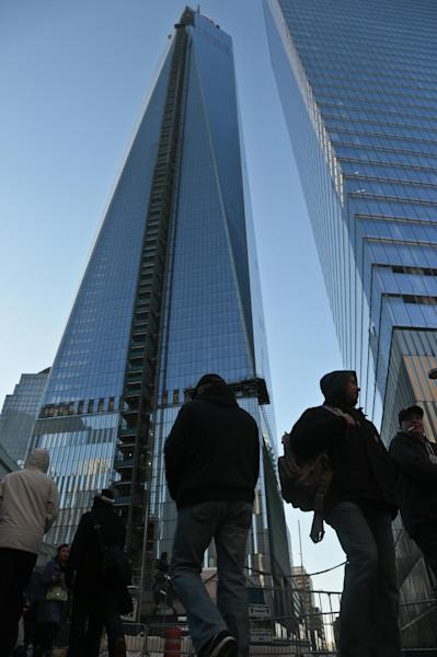 In this Tuesday, Feb. 11, 2014 photo, pedestrians pass a closed walkway next to 1 World Trade Center, left, in New York. The new 1 World Trade Center, the nation's tallest building, was recently cordoned off so pedestrians could avoid injury from falling ice. (AP Photo/Bebeto Matthews)