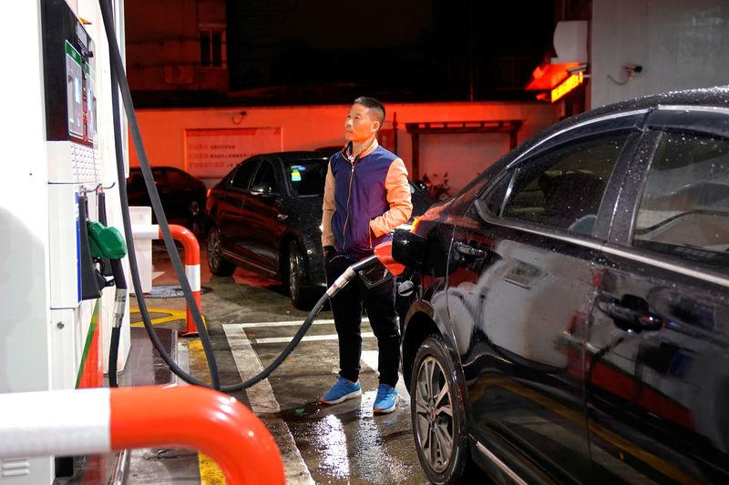 A driver looks at the price as he fills the tank of his car at a gas station in Shanghai
