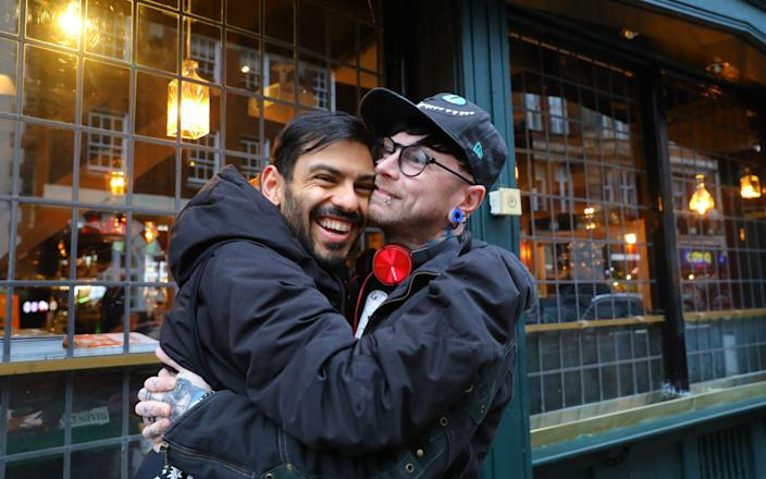 Friends hug outside a restaurant in London as Britain eased some coronavirus restrictions on Monday - VICKIE FLORES/EPA-EFE/Shutterstock