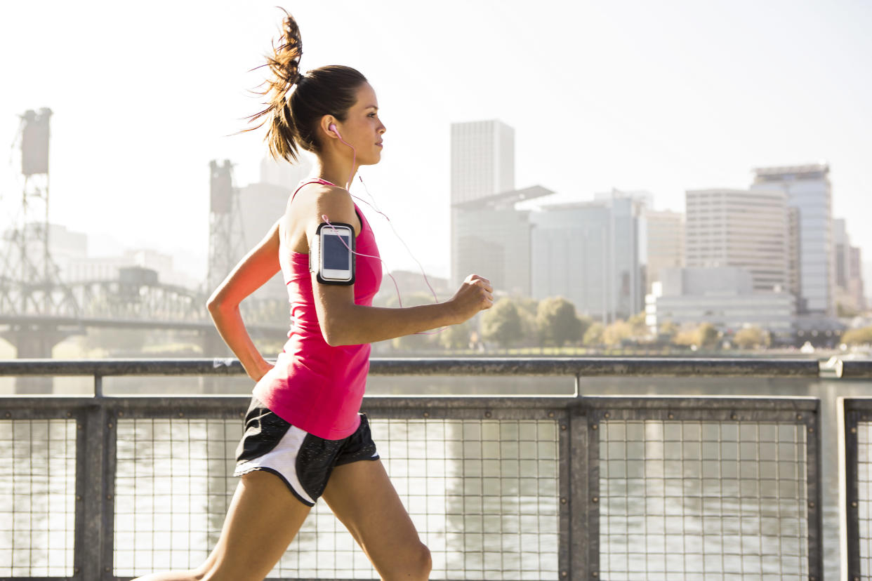A female listening to music and jogging across a bridge in Portland, Oregon.