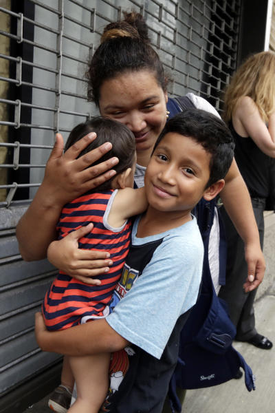 FILE - In this Friday, Aug. 3, 2018 file photo, Honduran Nahun Eduardo Puerto Pineda, then 8, holds his 2-year-old sibling after being reunited with his mother, Eilyn Carbajal, at the Cayuga Center, in New York. Fearful immigrant families hoping to reunite with children and teenagers who crossed the border alone are facing an intimidating system that includes submitting fingerprints by all adults in the household where a migrant child will live. Under new rules, the finger prints are shared with Immigration and Customs Enforcement. (AP Photo/Richard Drew)