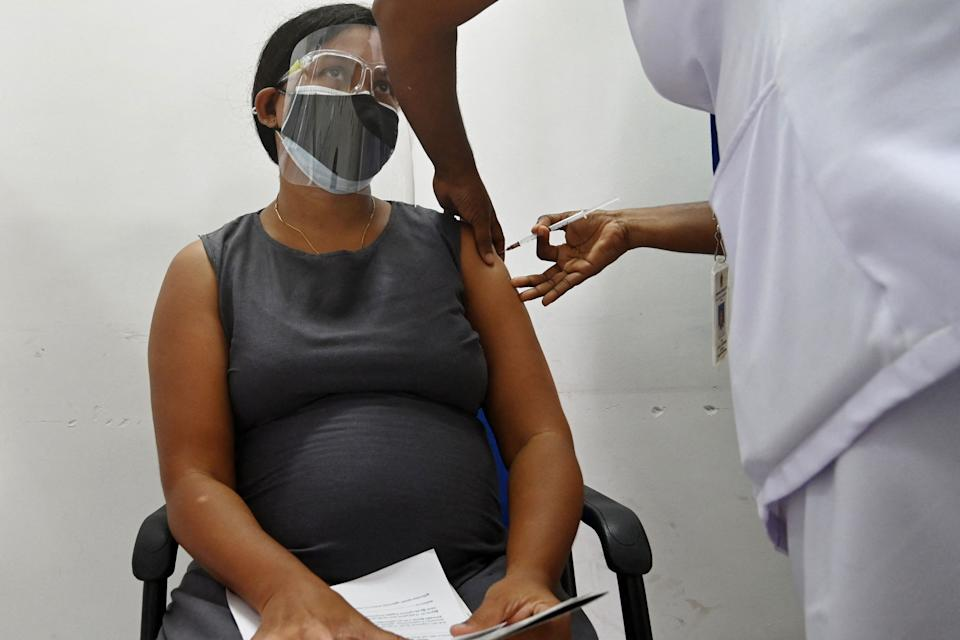 A health worker inoculates a pregnant women with a dose of the Chinese-made Sinopharm Covid-19 coronavirus vaccine after the government imposed a lockdown with travel restrictions to curb the spread of Covid-19 coronavirus, in Colombo on June 9, 2021. (Photo by LAKRUWAN WANNIARACHCHI / AFP) (Photo by LAKRUWAN WANNIARACHCHI/AFP via Getty Images)