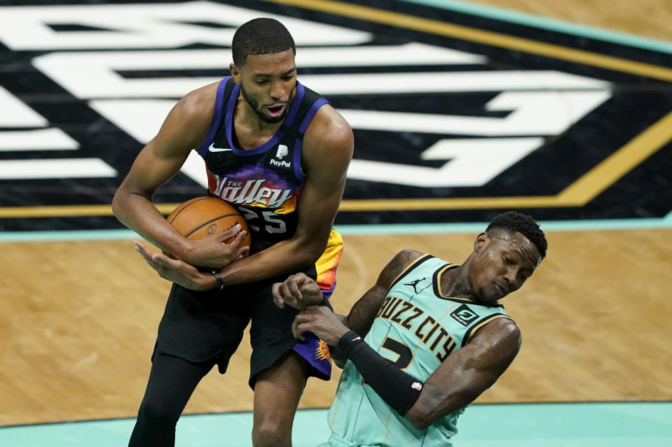 Phoenix Suns forward Mikal Bridges pulls a rebound away from Charlotte Hornets guard Terry Rozier during the first half of an NBA basketball game on Sunday, March 28, 2021, in Charlotte, N.C. (AP Photo/Chris Carlson)