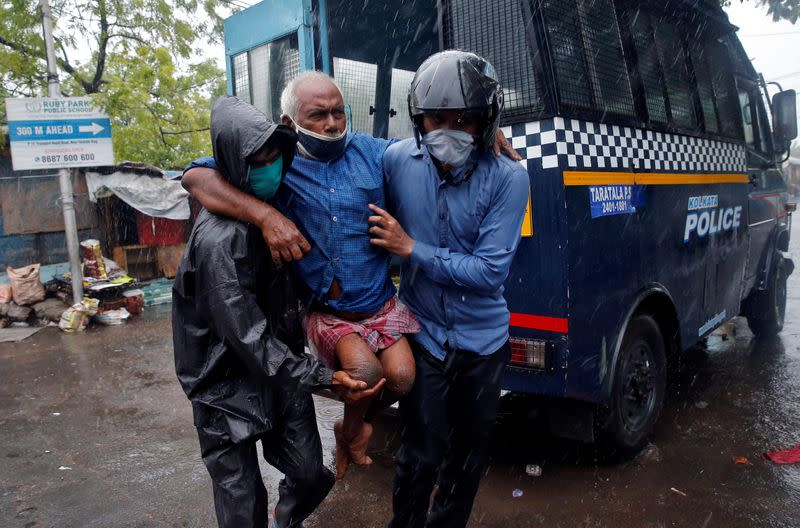 Police officers carry a disabled man to a safer place before Cyclone Amphan makes its landfall, in Kolkata