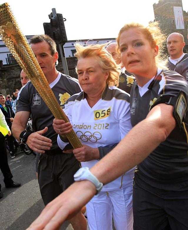 The Olympic torch bearer is re-routed by Olympic securtiy personall after protestors tussle with police near Peace Bridge in Londonderry , Northern Ireland on June 4, 2012. The Olympic Torch relay started at Land's End, the southwest tip of England, to begin an 8,000-mile (12,875-kilometre) journey around Britain, with a detour to also visit the Irish capital Dublin. It will culminate in the flame being brought to the Olympic Stadium for the opening of the Games on July 27.AFP PHOTO / PETER MUHLYPETER MUHLY/AFP/GettyImages