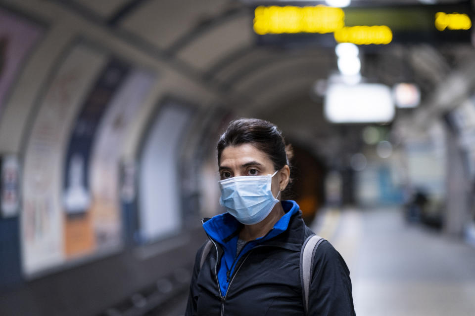 A middle-aged woman with dark hair using a health mask on the London Underground metro system during the Coronavirus outbreak