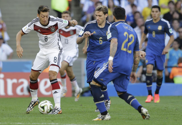 Germany's Mesut Ozil, left, controls the ball as Argentina's Ezequiel Lavezzi, right, and Argentina's Lucas Biglia (6) watch him, during the World Cup final soccer match between Germany and Argentina at the Maracana Stadium in Rio de Janeiro, Brazil, Sunday, July 13, 2014. (AP Photo/Victor R. Caivano)