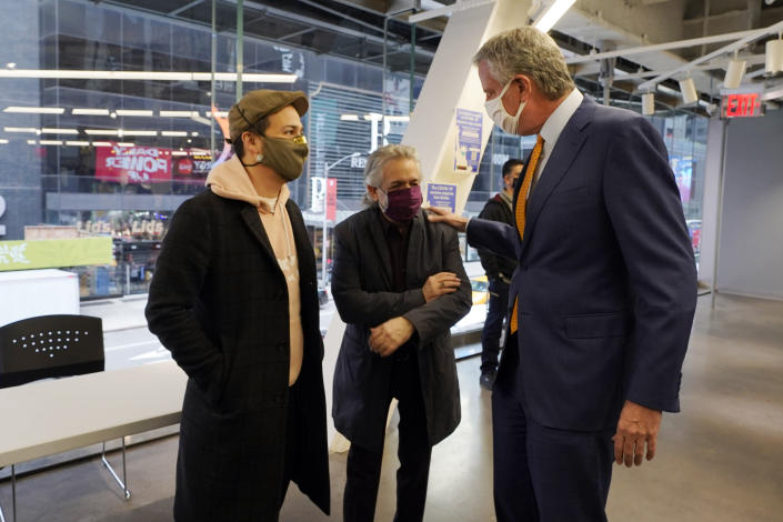 Actor Lin-Manuel Miranda, left, and his father, Luis A. Miranda, Jr., center, talk with New York Mayor Bill de Blasio, before they tour the grand opening of a Broadway COVID-19 vaccination site intended to jump-start the city's entertainment industry, in New York, Monday, April 12, 2021. (AP Photo/Richard Drew, Pool)