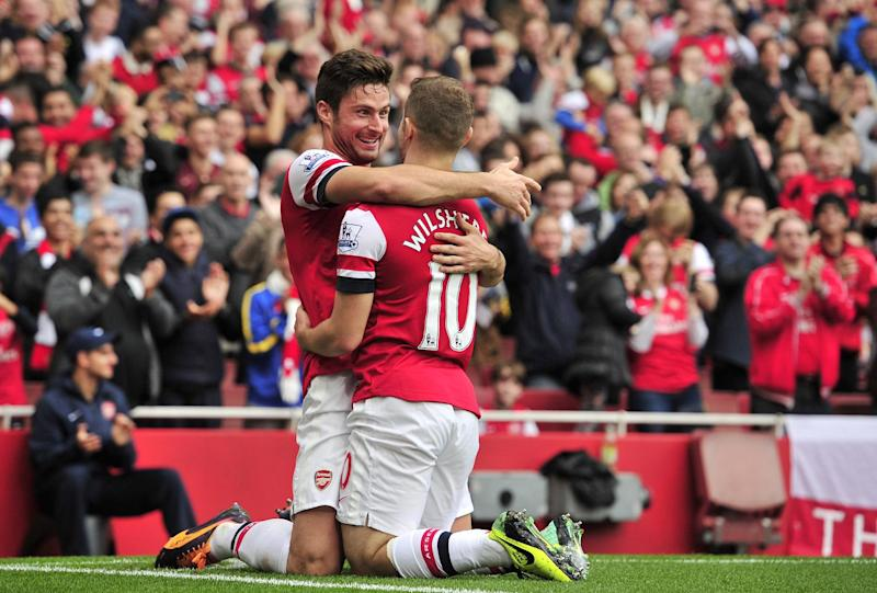 A file photo shows Arsenal midfielder Jack Wilshere (R) being congratulated by a teammate after he scored during a match against Norwich in London, October 2013 (AFP Photo/Glyn Kirk)