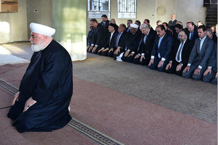 In this photo released on September 12, 2016 by the Syrian official news agency SANA, Syrian President Bashar Assad, right background, prays during Eid al Adha prayers behind Damascus Mufti Adnan Afiouni, foreground, in Daraya town suburb of Damascus, Syria. Mufti Afiouni who played a key role in government deals with rebel fighters, was killed on Thursday Oct. 22, 2020 by an explosion in the town of Qudsaya, west of Damascus, Syria, when a roadside bomb exploded near him, according to state media and a government site. (SANA via AP)