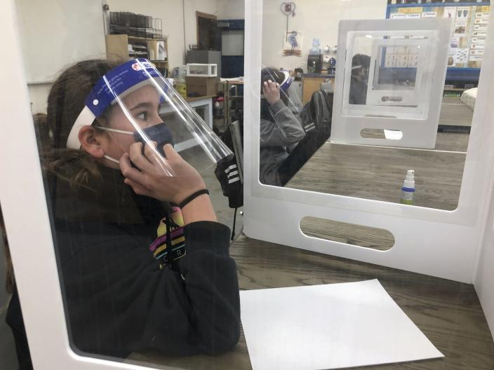 Students wearing face masks and face shields to protect from covid-19 sit at their desks during class at the Sinaloa Middle School in Novato, Calif. on Tuesday, March 2, 2021. The school just reopened Monday, Feb. 22, 2021 for in-person learning.(AP Photo/Haven Daily)