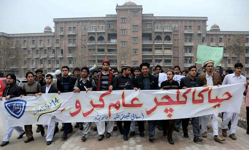 """University students affiliated with Pakistani religious party Jamaat-e-Islami rally against Valentine's Day holding a banner reading """"spread the culture of modesty,"""" on Thursday, Feb. 14, 2013 in Peshawar, Pakistan. Romance may not be dead in Pakistan but it is under attack. Conservatives in Pakistan are attacking the romantic holiday as a western-inspired event helping to spread vulgarity in their country and putting up posters calling on people to boycott the holiday. But romantics are fighting back with an arsenal of flowers, pink teddy bears and heart-shaped balloons. (AP Photo/Mohammad Sajjad)"""