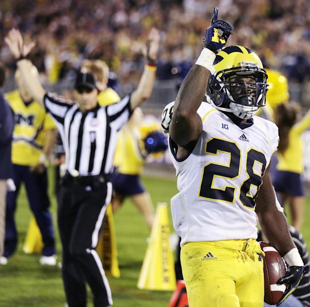 Michigan running back Fitzgerald Toussaint (28) celebrates after his fourth-quarter touchdown against Connecticut in an NCAA college football game, Saturday, Sept. 21, 2013, in East Hartford, Conn. Michigan won 24-21. (AP Photo/Charles Krupa)