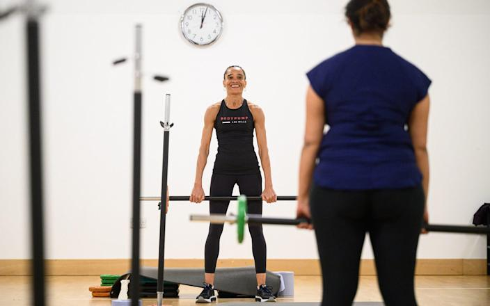 Fitness instructor Melanie Pennicott leads a group in a high energy barbell class just after midnight at an indoor group exercise studio at Park Road Pools & Fitness on May 17 in London - Leon Neal/Getty