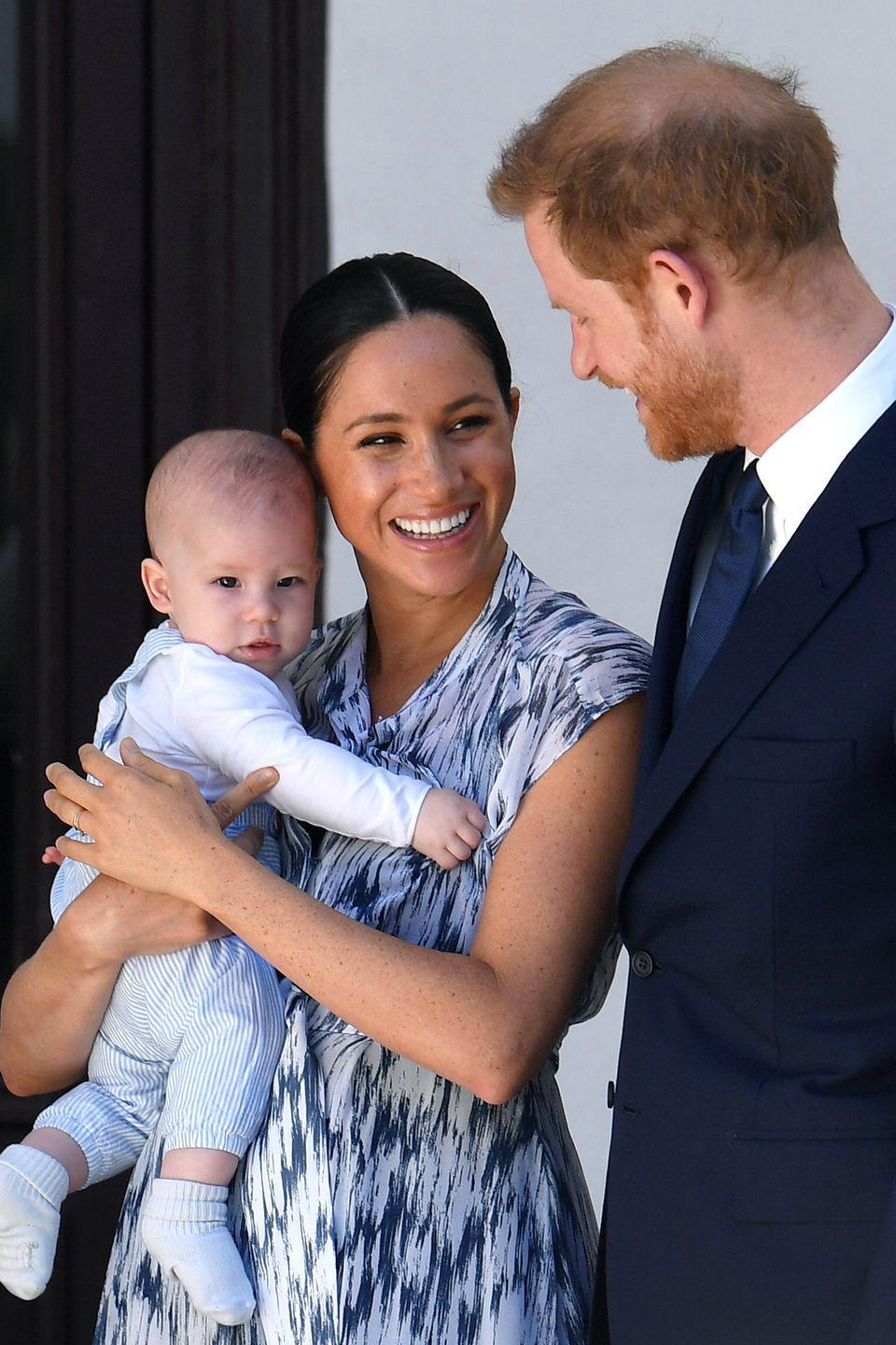 <p>Holding baby Archie, Meghan laughs while Harry looks down at the mother-son duo in Cape Town, South Africa.</p>
