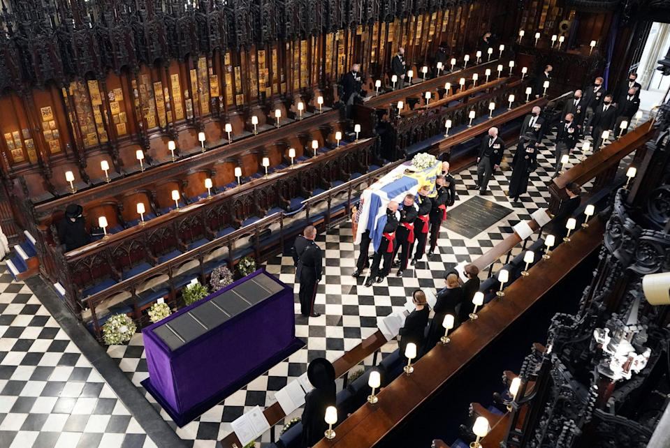 Britain's Queen Elizabeth II watches as pallbearers carry the coffin of the Duke of Edinburgh during his funeral at St. George's Chapel in Windsor Castle.