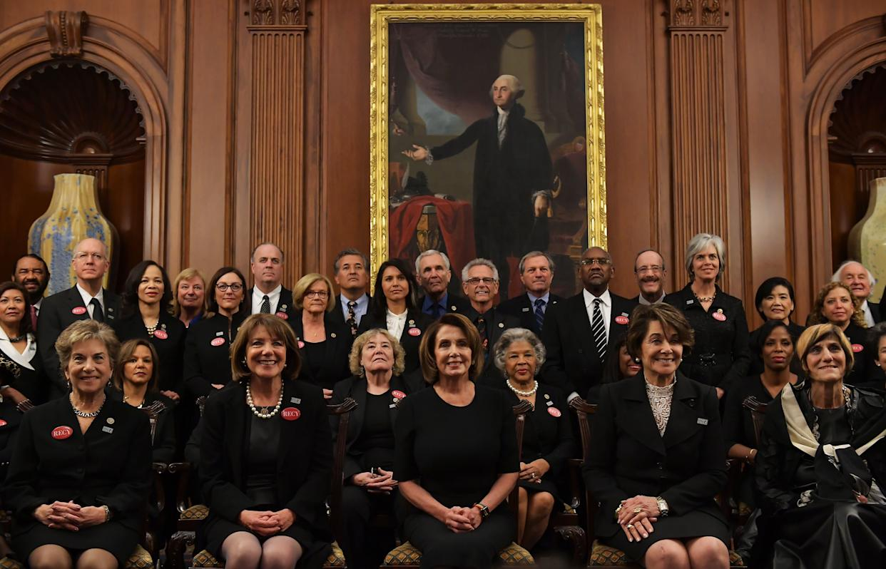 """House Minority Leader Nancy Pelosi (D-Calif.), center, poses with members of Congress wearing black in support of the """"Me Too"""" movement."""