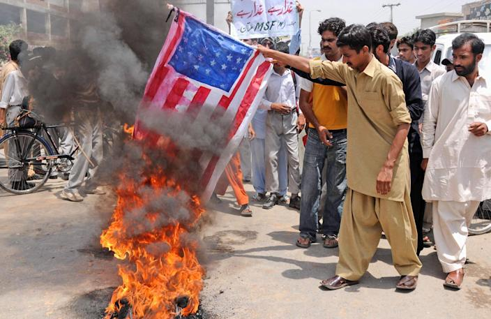 FILE - In this May 9, 2011 file photo, supporters of Pakistan's Muslim League burn a representation of the US flag during an anti American demonstration in Multan, Pakistan. The White House has no intentions to end CIA drone strikes against militant targets on Pakistani soil, setting the two countries up for diplomatic blows after Pakistani's parliament unanimously approved new guidelines for the country in its troubled relationship with the US, US and Pakistani officials say. (AP Photo/Khalid Tanveer, File)