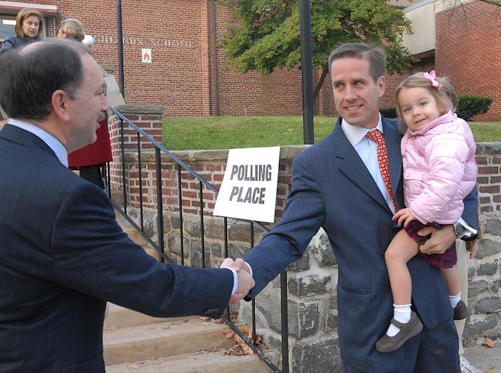 Delaware Democratic Attorney General candidate Beau Biden, holding his daughter Natalie, greets Gary Linarducci after placing his vote in Wilmington, Del., Tuesday, Nov. 7, 2006 (AP Photo/Pat Crowe II)