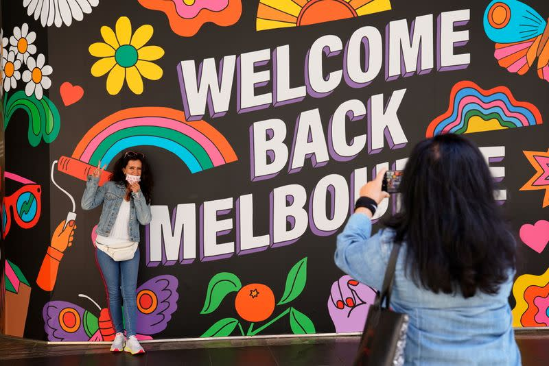 People take photos in front of a 'Welcome Back' sign after coronavirus disease restrictions were eased in Melbourne
