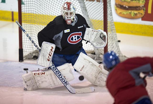 Montreal Canadiens goalie Dustin Tokarski stops a shot during an optional practice Monday, May 26, 2014 in Brossard, Quebec. The Canadiens will face the New York Rangers Tuesday in Game 5 of the NHL hockey Eastern Conference Finals. The Rangers lead the best-of-seven series 3-1. (AP Photo/The Canadian Press, Paul Chiasson)