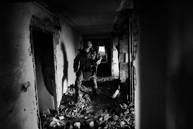 <p>A Ukrainian soldier advances to his position within a damaged hospital in Marynka, Ukraine, April 2017. (Photo: Manu Brabo/MeMo) </p>