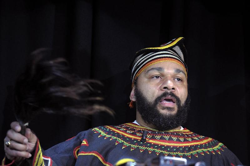 Controversial French comedian Dieudonne M'bala M'bala holds a fly-whisk as he gives a press conference in the Theatre de la Main d'or in Paris on January 11, 2014