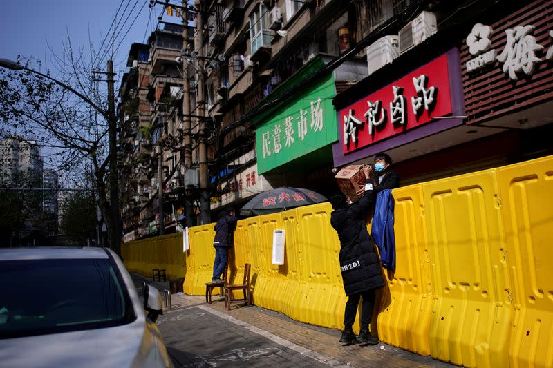 Residents pay for groceries over barriers set up to ring fence a wet market on a street in Wuhan