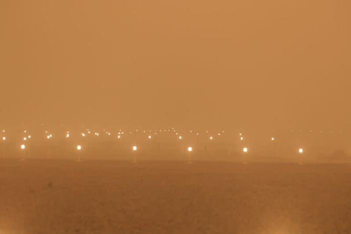 """A view of the runway during a sandstorm blown over from North Africa known as """"calima"""" at Las Palmas Airport"""