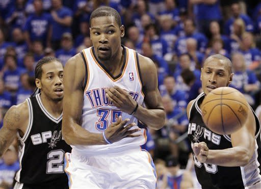 Oklahoma City Thunder forward Kevin Durant (35) passes the ball after splitting San Antonio Spurs defenders Kawhi Leonard (2) and Boris Diaw (33) during the first half of Game 4 in the NBA basketball playoffs Western Conference finals, Saturday, June 2, 2012, in Oklahoma City. (AP Photo/Sue Ogrocki)