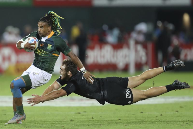 South Africa's Rosko Specman misses a tackle by New Zealand's player in the final match of the Emirates Airline Rugby Sevens in Dubai, United Arab Emirates, Saturday, Dec.7, 2019. (AP Photo/Kamran Jebreili)