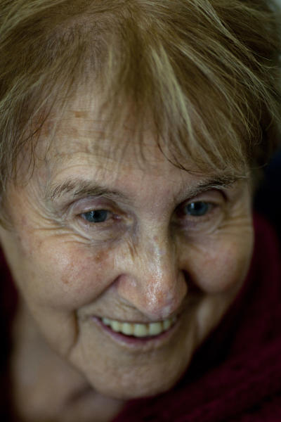 """Holocaust survivor Stella Knobel, smiles as she speaks during a new exhibition of Israel's national Holocaust memorial and museum in Jerusalem, Sunday, Jan. 27, 2013. When Stella Knobel's family had to flee World War II Poland in 1939, the only thing the 7-year-old girl could take with her was her teddy bear. For the next six years, the stuffed animal never left her side as the family wondered through the Soviet Union, to Iran and finally the Holy Land. """"He was like family. He was all I had. He knew all my secrets,"""" the 80-year-old now says with a smile. """"I saved him all these years. But I worried what would happen to him when I died."""" So when she heard about a project launched by Israel's national Holocaust memorial and museum to collect artifacts from aging survivors - before they, and their stories, were lost forever - she reluctantly handed over her beloved bear Misiu - Polish for """"Teddy Bear""""- so the fading memories of the era could be preserved for others. (AP Photo/Ariel Schalit)"""