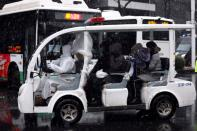 Worker in protective suit drives a vehicle amid snow to transport novel coronavirus patients outside a hospital in Wuhan
