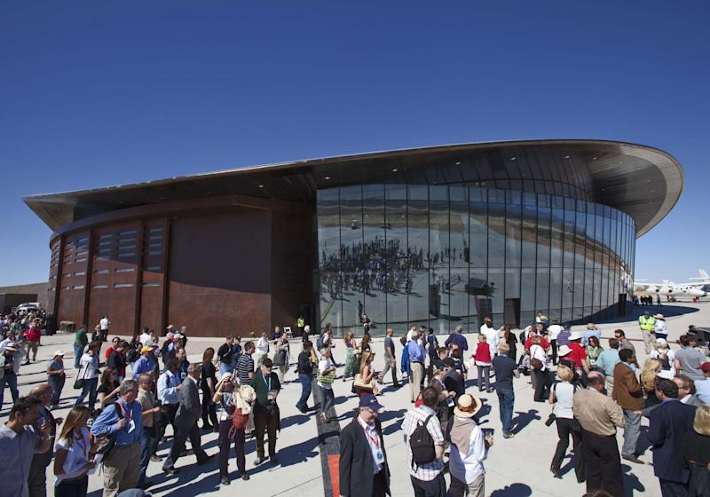 FILE - In this Oct. 17, 2011 file photo, guests stand outside the new Spaceport America hangar in Upham, N.M. With Spaceport nearly complete but still mostly empty, Branson and Virgin Galactic has hinted it may take its spacecraft and launch elsewhere.  (AP Photo/Matt York, File)