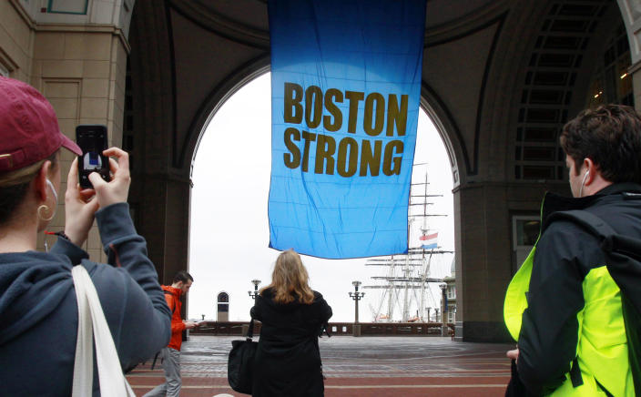 """People photograph a banner reading """"Boston Strong"""" as it hangs at Rowes Wharf on the first anniversary of the Boston Marathon bombings, Tuesday, April 15, 2014, in Boston. (AP Photo/Bill Sikes)"""