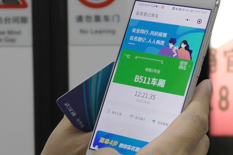 """In this April 1, 2020, photo, a passenger holds up a green pass on their phone on a subway train in Wuhan in central China's Hubei province. Green is the """"health code"""" that says a user is symptom-free and it's required to board a subway, check into a hotel or just enter Wuhan, the central city of 11 million people where the pandemic began in December. (AP Photo/Olivia Zhang)"""