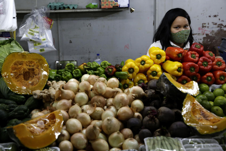 A vegetable vendor wears a mask amid the COVID-19 pandemic as the local government allows the reopening of markets and street fairs in Brasilia, Brazil, Friday, July 3, 2020. (AP Photo/Eraldo Peres)