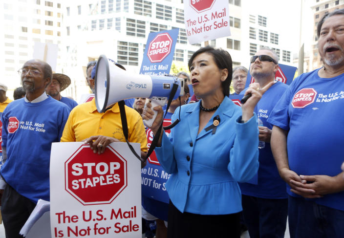 U.S. Congresswoman Judy Chu (D-Calif.) joins U.S. Post Office employees during a protest outside a Staples store, Thursday, April 24, 2014, in downtown Los Angeles. Postal workers around the country protested in front of Staples stores on Thursday, objecting to the U.S. Postal Service's pilot program to open counters in stores, staffed with retail employees. (AP Photo/Damian Dovarganes)